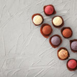 stock-photo-assorted-chocolate-truffles-on-textured-background-780782083